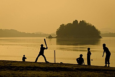 Teenagers playing cricket, the national game of India, on the bank of the Brahmaputra river, Peacock Island and the Uma Nanda Temple at the back, Guwahati, Assam, India, Asia