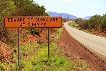 Warning sign, Beware of sunglare at sunrise, next to a road, Pilbara, Western Australia, Australia