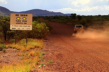 Warning sign, Turn your lights on, next to a road, Pilbara, Western Australia, Australia