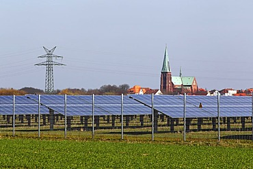 Solar power plant in a field in front of Meldorfer Cathedral, photovoltaic system, Meldorf, Dithmarschen, Schleswig-Holstein, Germany, Europe