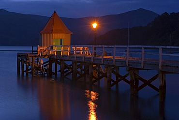 A pier and a lamp in twilight, in Akaroa, Banks Peninsula, Canterbury region, South Island, New Zealand