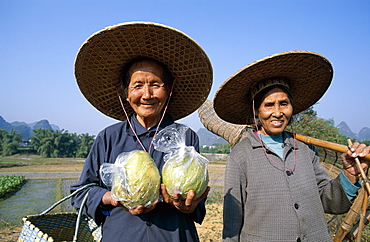Local women with pomelos and traditional fishing basket, Guilin, Yangshou, Guangxi Province, China, Asia