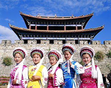 Bai Minority women dressed in Bai traditional costume in front of Town walls and Old Town Gateway, Old Town, Dali, Yunnan Province, China, Asia