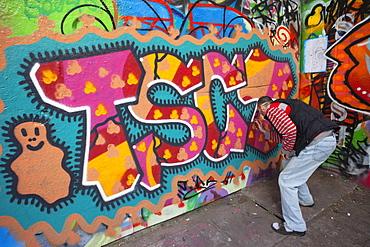 Graffiti artist at work under the Queen Elizabeth Hall, Southbank, London, England, United Kingdom, Europe