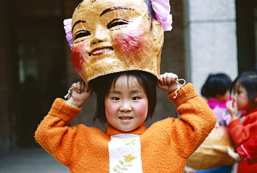 Young girl with Chinese Lucky God mask, Beijing, China, Asia