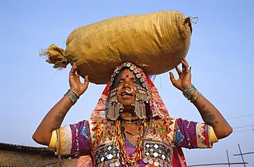 Gypsy woman carrying sack on head, Goa, India, Asia