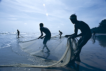 Silhouettes of fishermen pulling in nets, Negombo Beach, Negombo, Sri Lanka, Asia