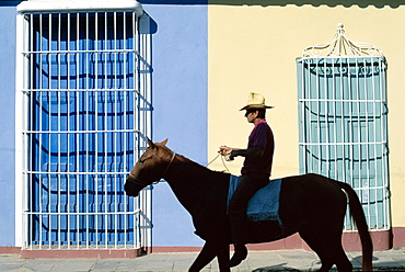 Man riding horse past colonial grille windows, Trinidad, UNESCO World Heritage Site, Cuba, West Indies, Central America