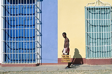 Man walking past colonial grille windows, Trinidad, UNESCO World Heritage Site, Cuba, West Indies, Central America