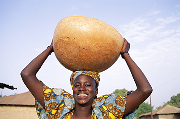 African woman carrying gourd on head, Banjul, Gambia, West Africa, Africa