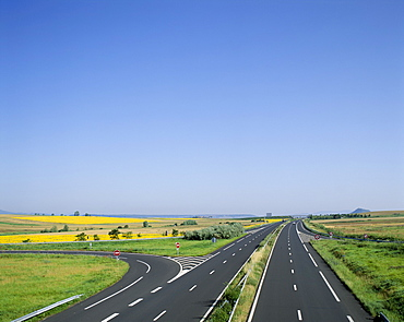 Empty highway with fields of sunflowers in distance, France, Europe