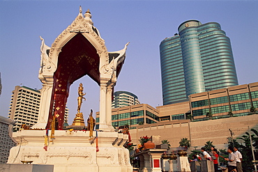 People praying at the Central World Plaza Shopping Centre Shrine with Gaysorn Shopping Mall in the background, Bangkok, Thailand, Southeast Asia, Asia