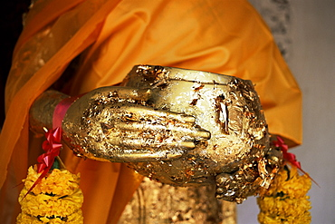 Detail of Buddha statue showing alms bowl covered in gold leaf, Nakhon Pathom Chedi, Nakhon Pathom, Thailand, Southeast Asia, Asia