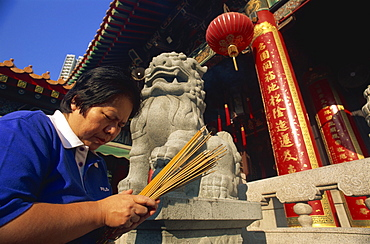 Woman praying with incense sticks, Wong Tai Sin Temple, Wong Tai Sin, Kowloon, Hong Kong, China, Asia
