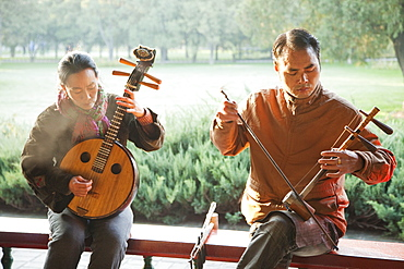 Man and woman playing traditional Chinese stringed instruments, Temple of Heaven Park, Beijing, China, Asia