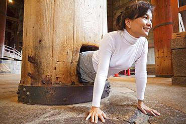 Tourist squeezing through the healing pillar for good health, Todaiji Temple, Nara, Japan, Asia