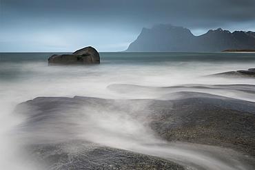 Water breaks over rocks at Uttakleiv, Lofoten Islands, Arctic, Norway, Scandinavia, Europe