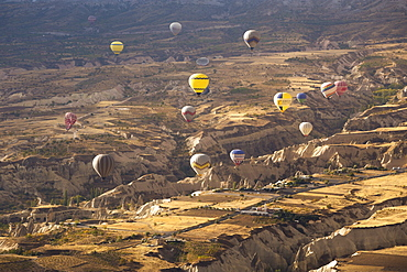 Hot air balloons above the volcanic landscape near Goreme, Cappadocia, Anatolia, Turkey, Asia Minor, Eurasia