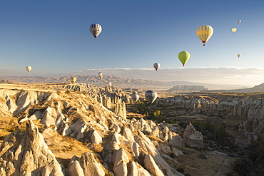 Hot air balloons over volcanic landscape in the dawn sky above Goreme, Cappadocia, Anatolia, Turkey, Asia Minor, Eurasia