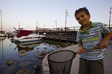 Cypriote boy fishing in a marina in Cyprus at dusk, Cyprus