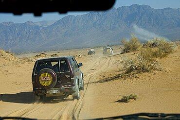 Photograph of a SUV driving through a sand dune in the Jordanian desert
