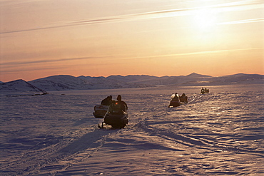 Image of a convoy of motorbikes on the ice plains of Baffin Canada