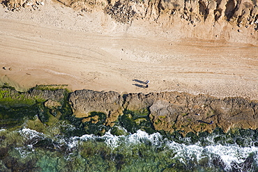 Aerial photograph of a copule strolling on the beach, Israel