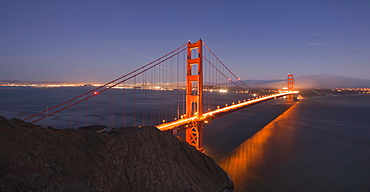 Golden Gate Bridge glowing at sunset with the San Francisco skyline behind, viewed from the Marin Headlands, San Francisco, California, United States of America, North America