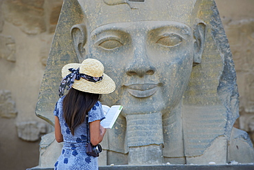 Tourist studying a statue of the pharaoh Ramesses II, Temple of Luxor, Luxor, Thebes, UNESCO World Heritage Site, Egypt, North Africa, Africa