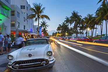 Ocean Drive restaurants, vintage car and Art Deco architecture at dusk, South Beach, Miami Beach, Miami, Florida, United States of America, North America