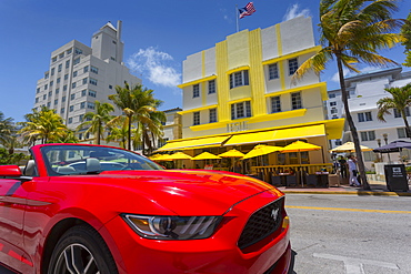 Art Deco architecture and red sports car on Ocean Drive, South Beach, Miami Beach, Miami, Florida, United States of America, North America