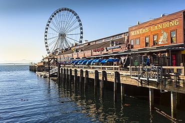 Seattle Great Wheel on Pier 57 in the foreground in late afternoon sunshine. Seattle, Washington State, United States of America, North America