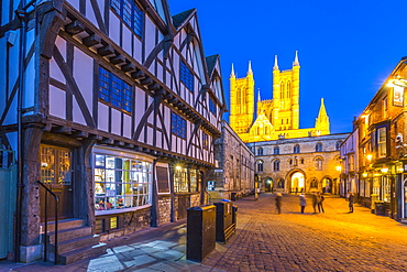 View of illuminated Lincoln Cathedral viewed from Exchequer Gate with timbered architecture of Visitors Centre at dusk, Lincoln, Lincolnshire, England, United Kingdom, Europe