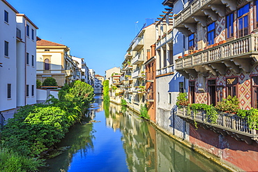 View of river lined by houses reflected in river, Padua, Veneto, Italy, Europe