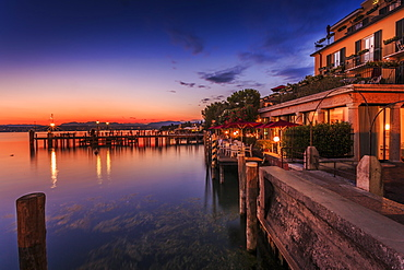 View of golden sunset and restaurant overlooking Lake Garda, Sirmione, Lake Garda, Lombardy, Italian Lakes, Italy, Europe