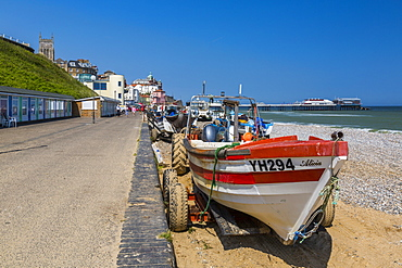 View of Cromer Pier and boats on shingle beach on a summer day, Cromer, Norfolk, England, United Kingdom, Europe
