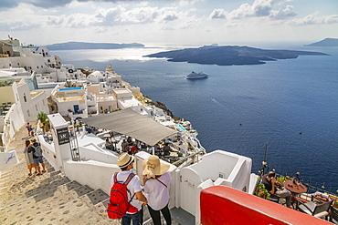 View of Fira restaurants and cruise ship, Firostefani, Santorini (Thira), Cyclades Islands, Greek Islands, Greece, Europe