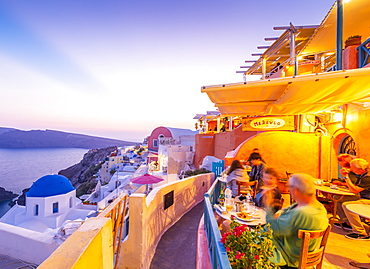 View of restaurant in Oia village overlooking the sea at dusk, Santorini, Cyclades, Aegean Islands, Greek Islands, Greece, Europe