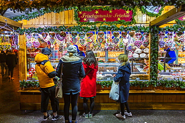 People shopping at Christmas market at night in Rathausplaza, Vienna, Austria, Europe