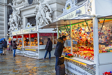 Shoppers at Christmas market stalls in Michaelerplatz, Vienna, Austria, Europe