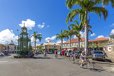 View of cyclists in The Circus and Memorial Clock, Basseterre, St. Kitts and Nevis, West Indies, Caribbean, Central America
