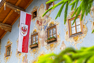 View of Austrian flag and colourful architecture in St. Johann in Tirol, Austrian Tyrol, Austria, Europe