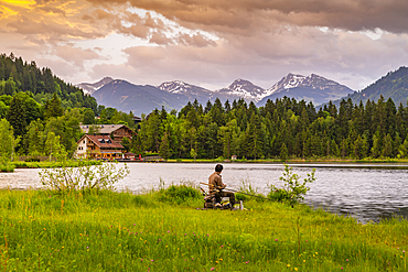 Fisherman and mountainous backdrop at Schwarzsee near Kitzbuhel, Tyrol, Austria, Europe