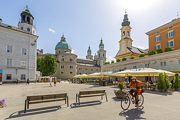 View of cyclist and Salzburg Cathedral in Residenzplatz, Salzburg, Austria, Europe