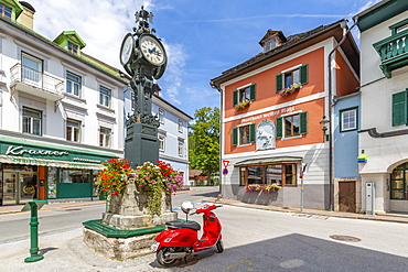 View of colourful buildings, red scooter and main street in Bad Aussie, Styria, Austria, Europe