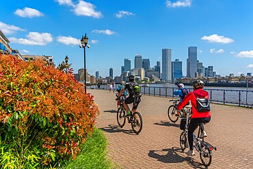 View of cyclists on the Thames Path at Wapping and Canary Wharf Financial District in the background, London, England, United Kingdom, Europe - 844-23658
