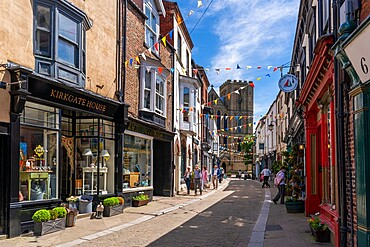 View of shops and cafes on Kirkgate and Cathedral in background, Ripon, North Yorkshire, England, United Kingdom, Europe