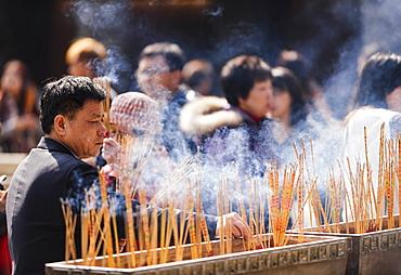 People burning incense outside Wong Tai Sin Temple, Kowloon, Hong Kong, China, Asia