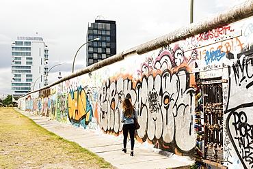 Young woman walking past graffiti on former Berlin Wall, East Side Gallery, Muhlenstrasse, Friedrichshain District, Berlin, Germany, Europe