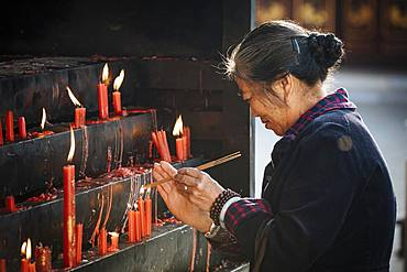 Woman lighting candles at Yuantong Buddhist Temple, Kunming, Yunnan Province, China, Asia